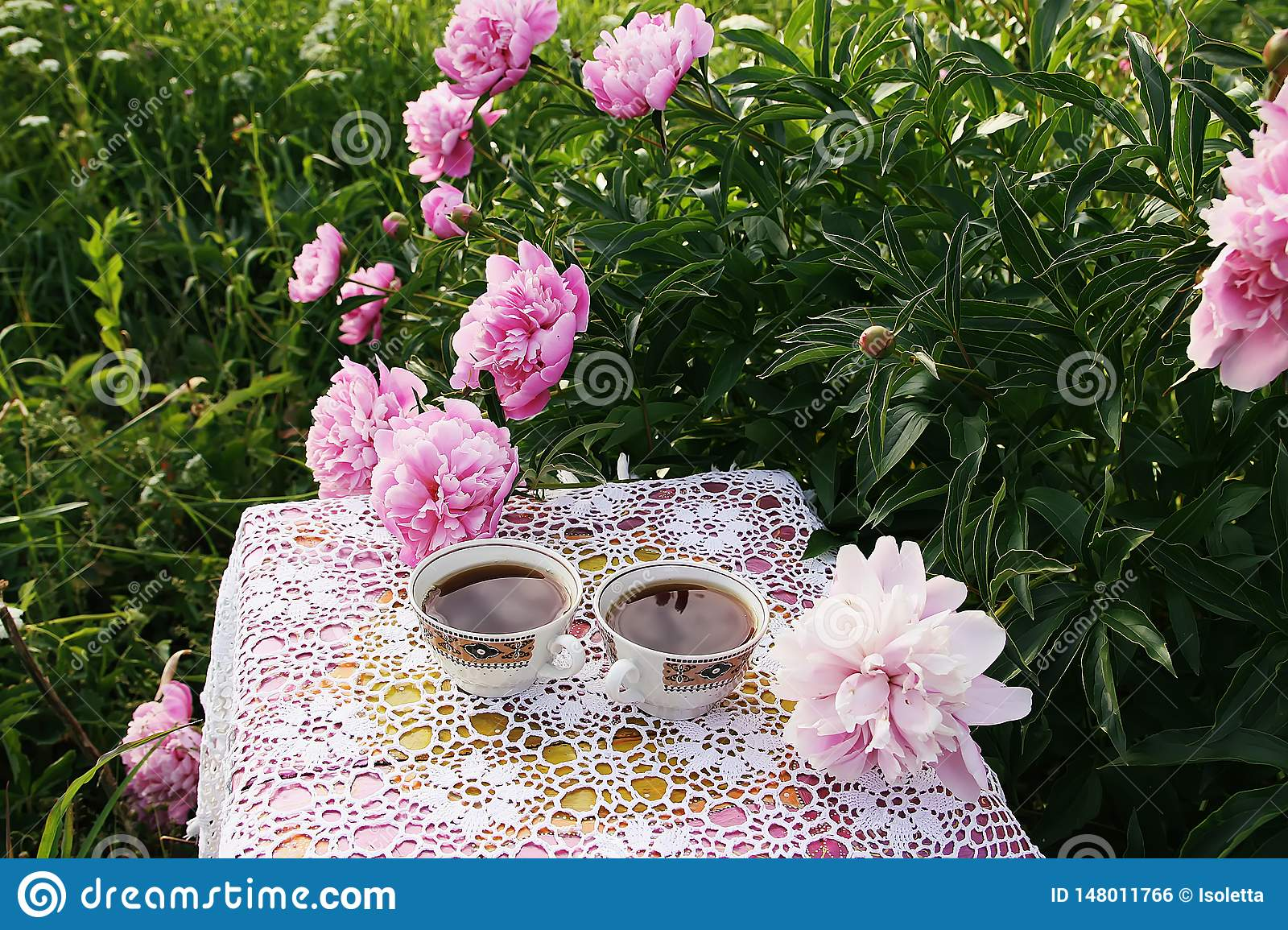 Tea in country style in summer garden in the village. Two cups of black tea on crocheted vintage lacy tablecloth and blooming