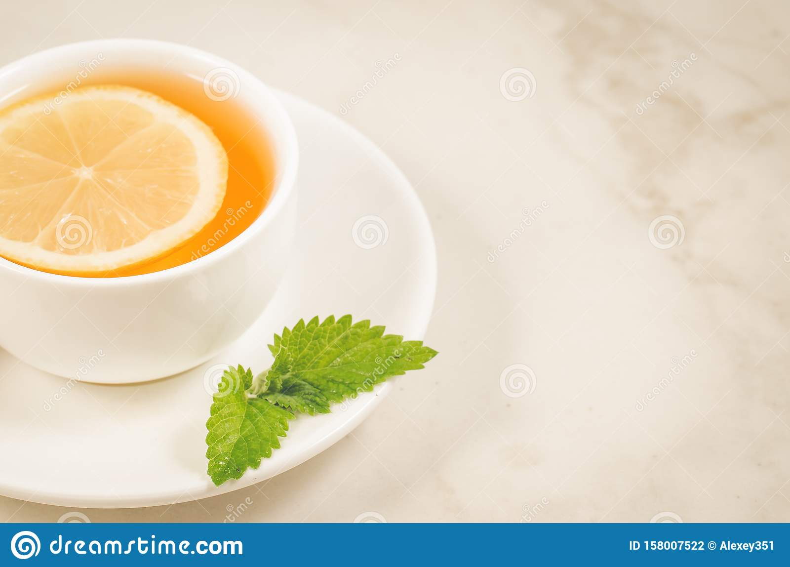 tea cup with a lemon and mint/tea cup with a lemon and mint on a white marble background. Selective focus and copy space