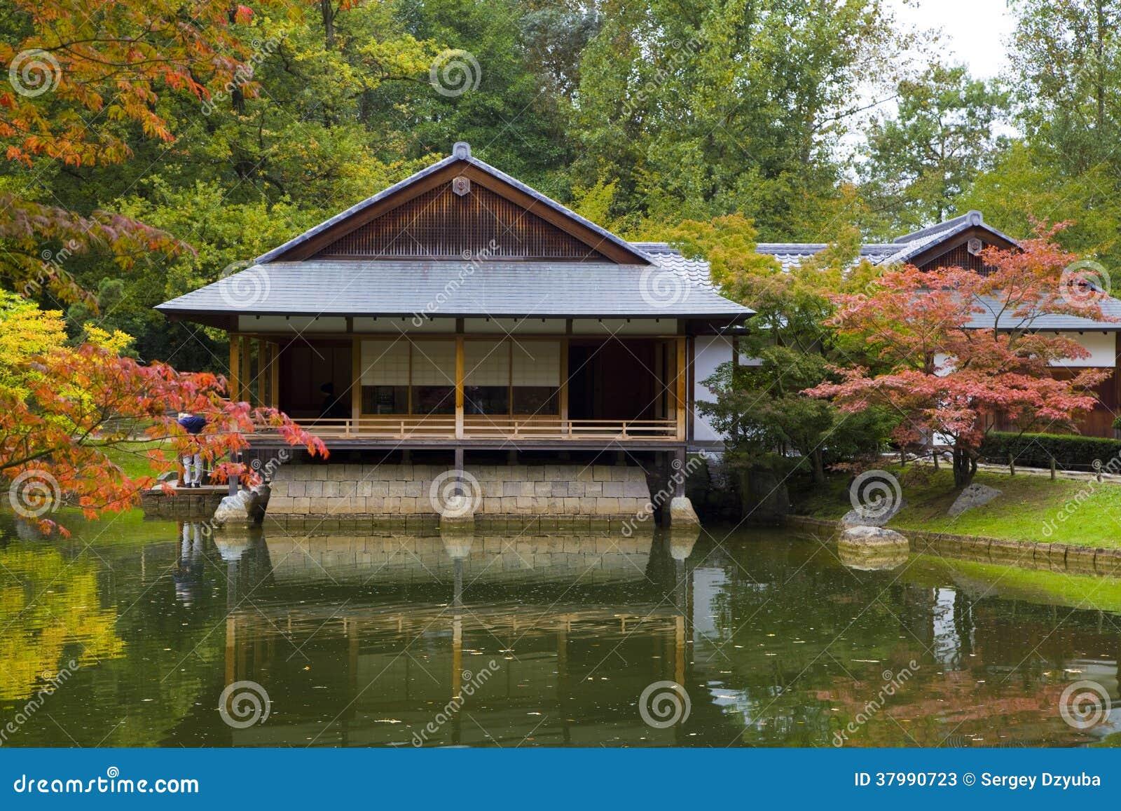 Tea house reflecting in pond in japanese garden stock for Japanese garden house