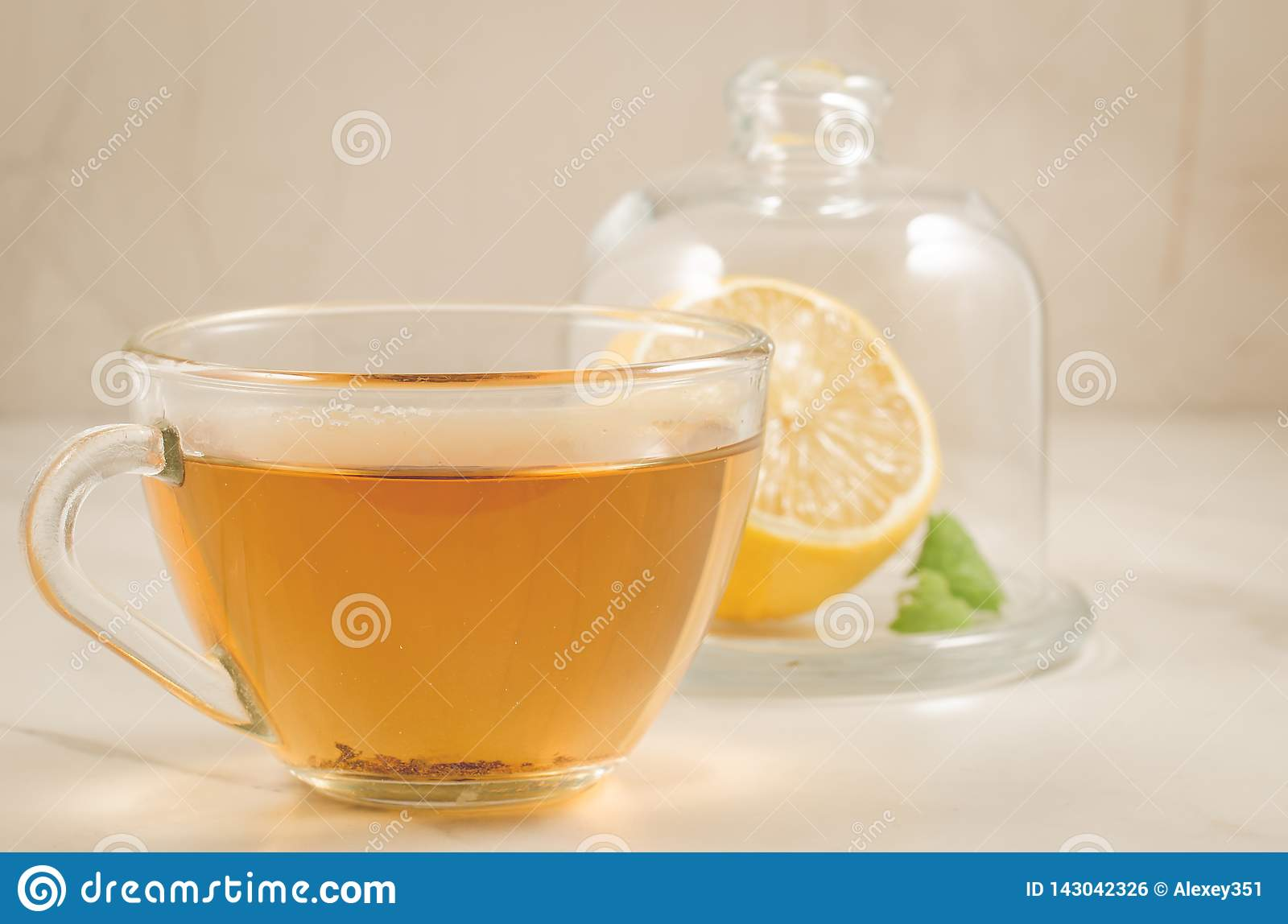 Tea with a lemon and mint in glass cup/tea with a lemon and mint in glass cup on a white table, selective focus