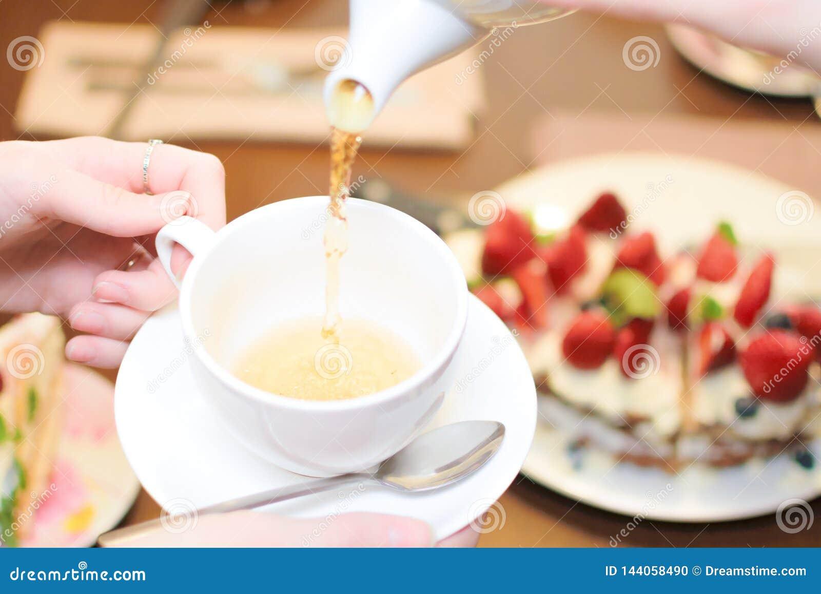 Tea party. Women pour green tea into a white Cup