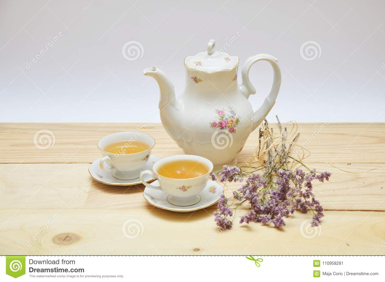 Tea pot and two cups on wooden table on white