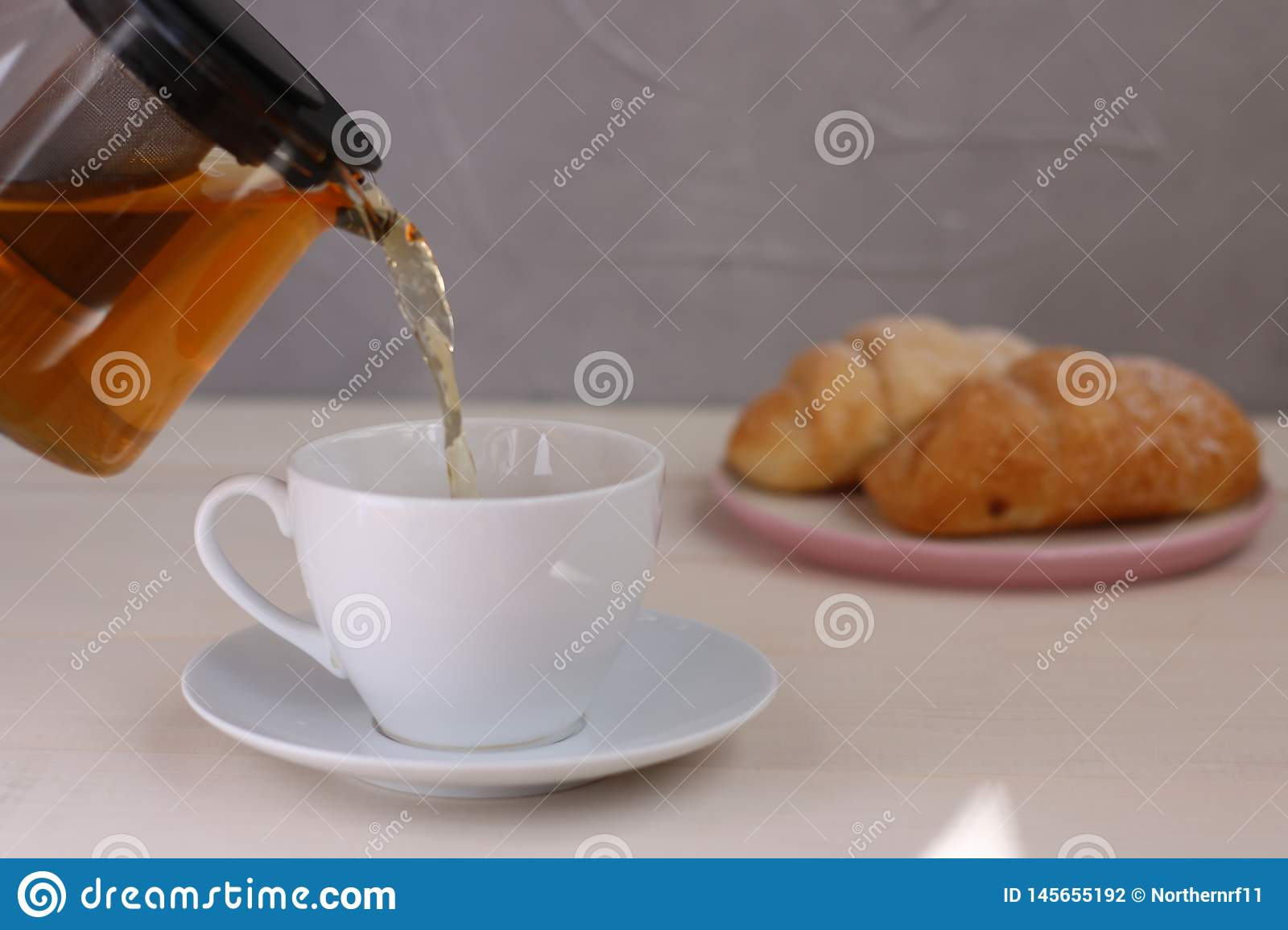 Tea pouring into cup and croissant dessert on light wooden background