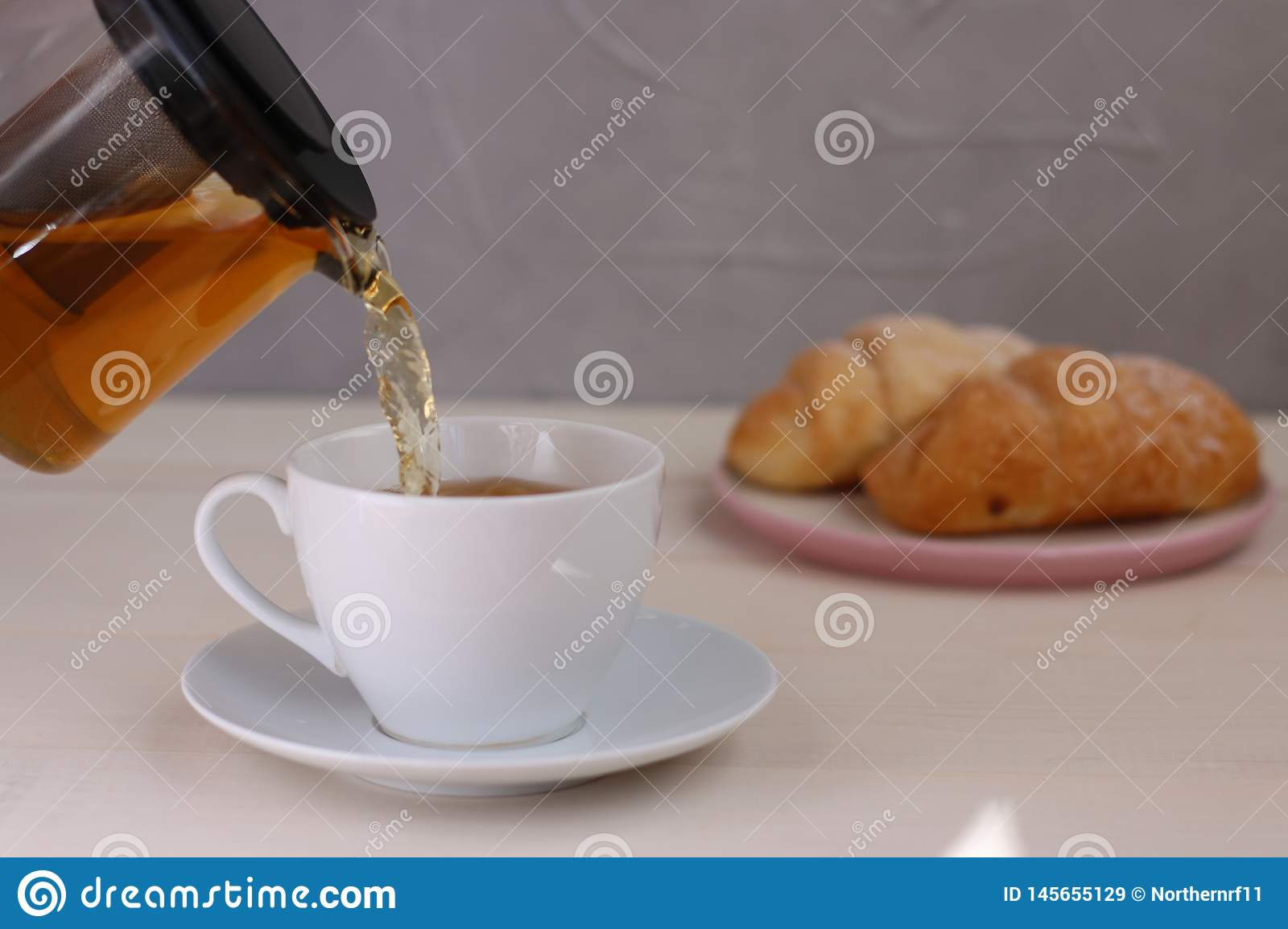 Tea pouring in cup on light background. teapot and breakfast concept