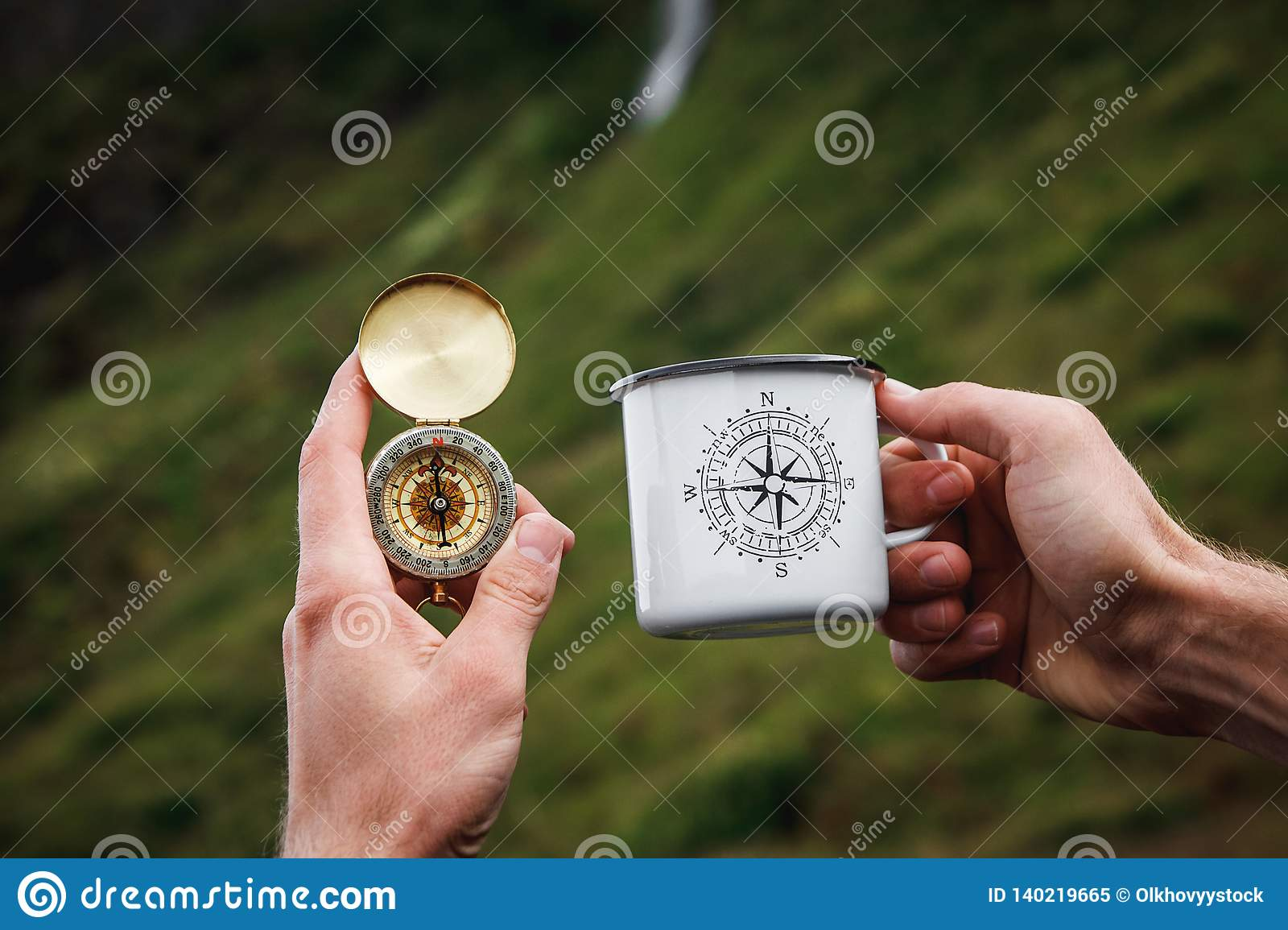 Tea in a tourist metal mug and a compass in Hand Natural background .Vintage Tone