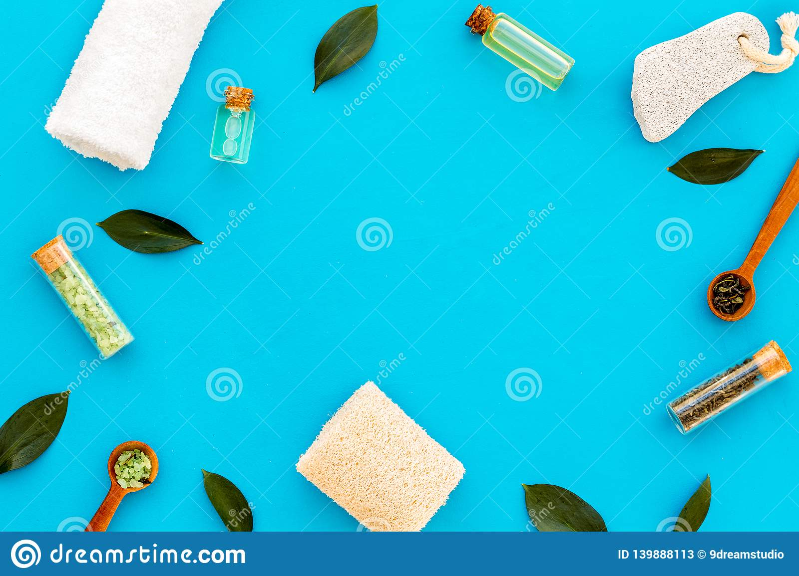 Tea tree spa composition. Fresh tea tree leaves, natural cosmetics, towel on blue background top view space for text