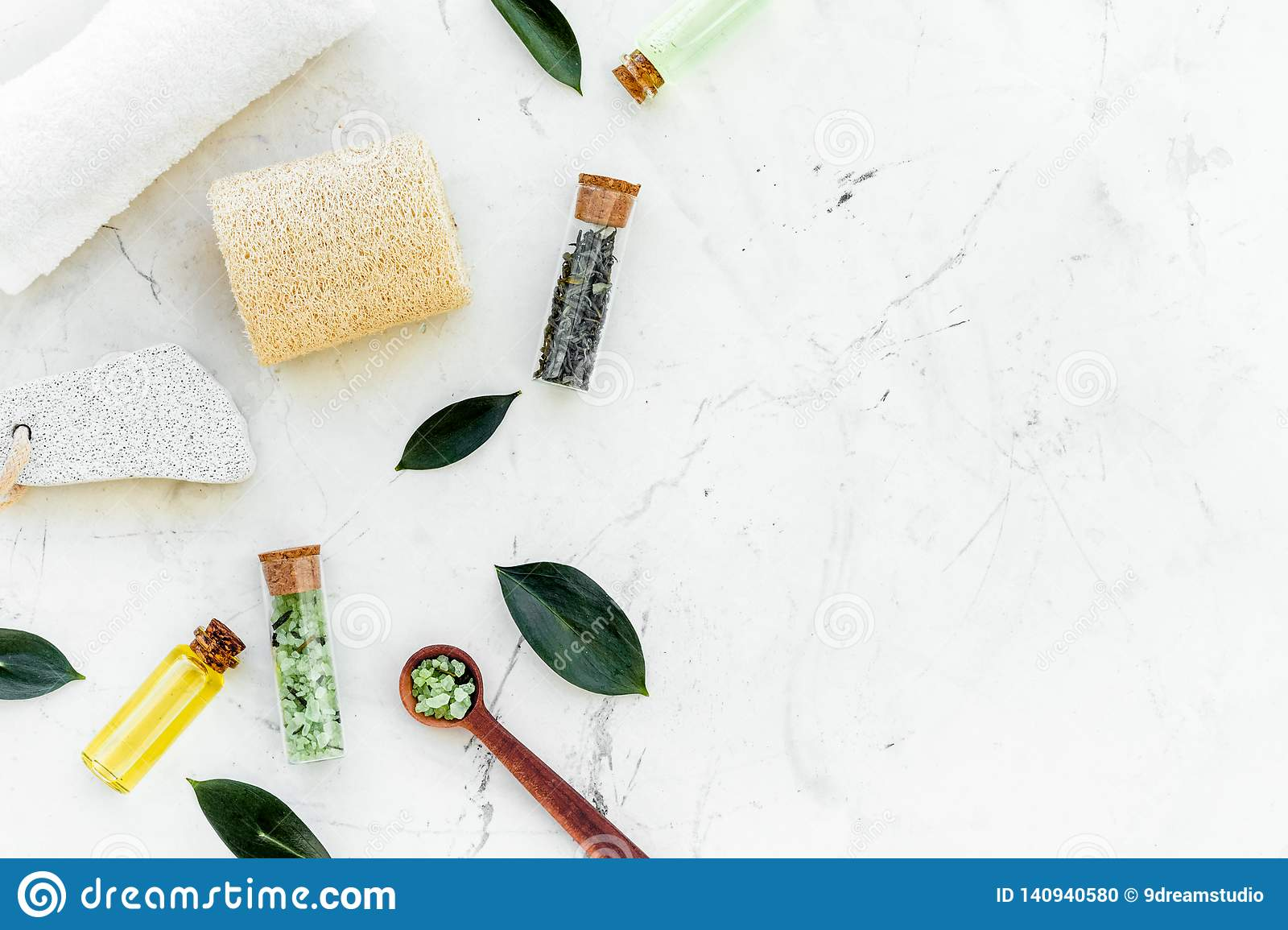 Tea tree spa composition. Fresh tea tree leaves, natural cosmetics, towel on white stone background top view copy space