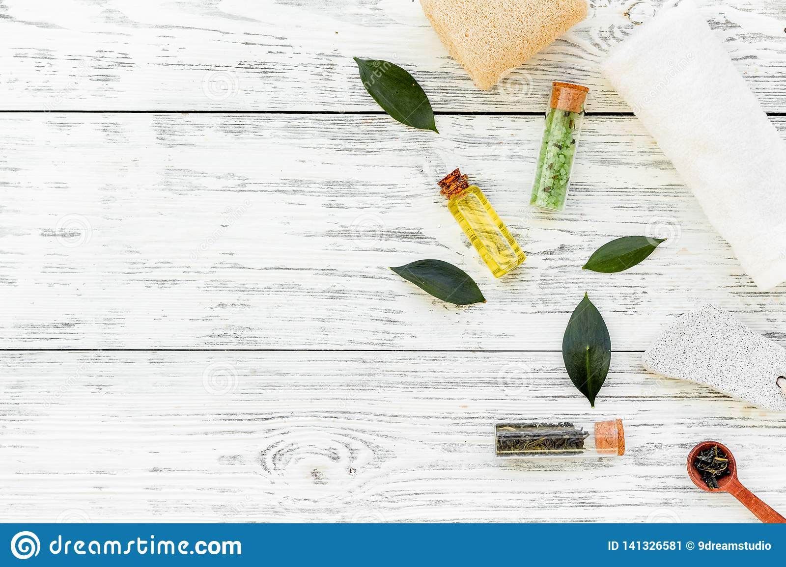 Tea tree spa composition. Fresh tea tree leaves, natural cosmetics, towel on white wooden background top view space for
