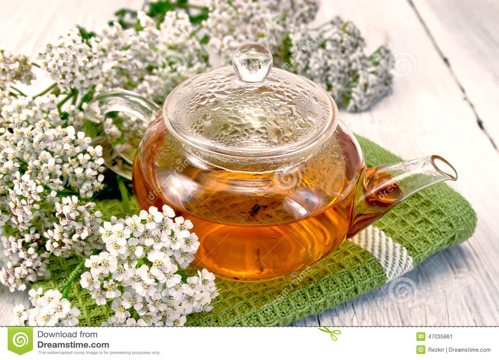 Tea with yarrow in glass teapot on napkin