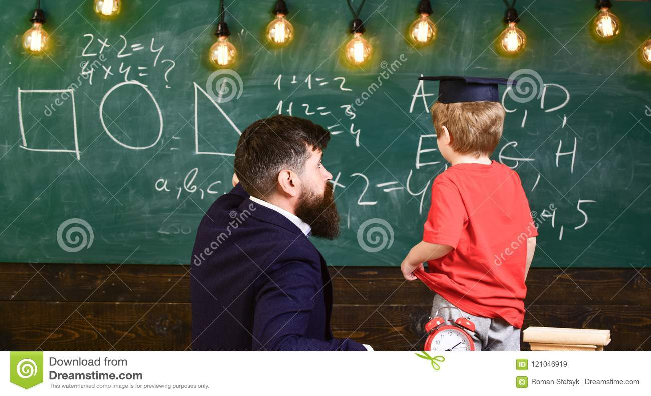 Individual education concept. Teacher and child turned back in the classroom. Boy listening to the explanation about