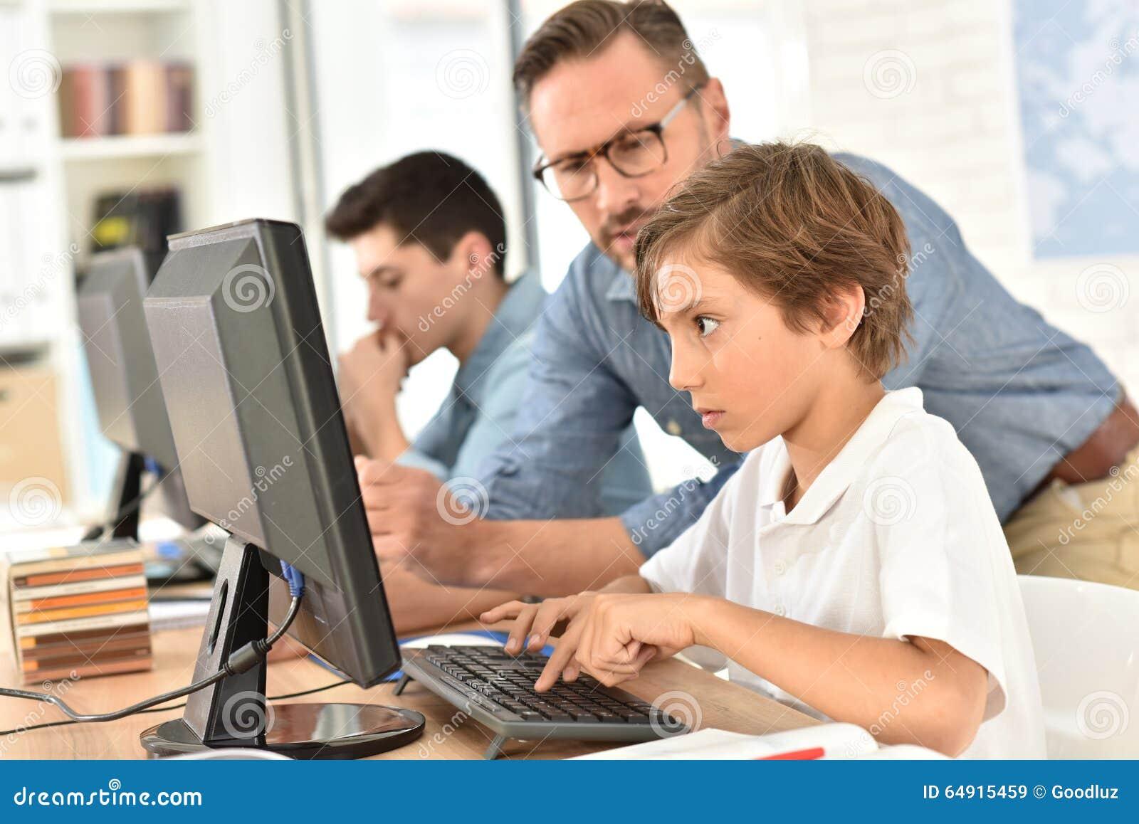 Teacher With Children Using Computer