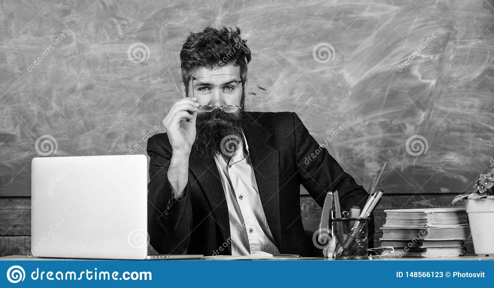 Teacher formal wear sit table classroom chalkboard background. Teacher concentrated bearded mature schoolmaster