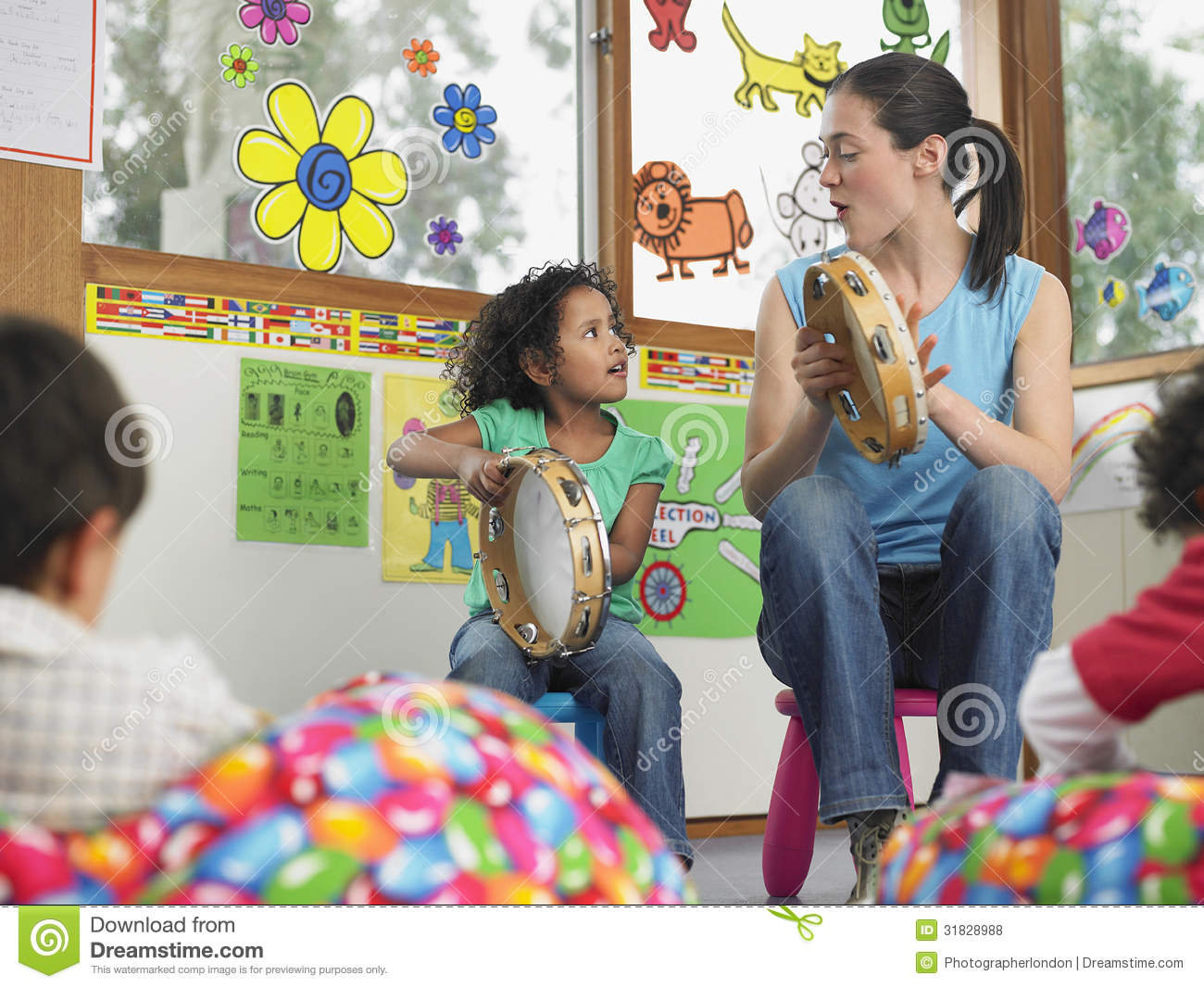 Teacher With Girl Playing Music In Class