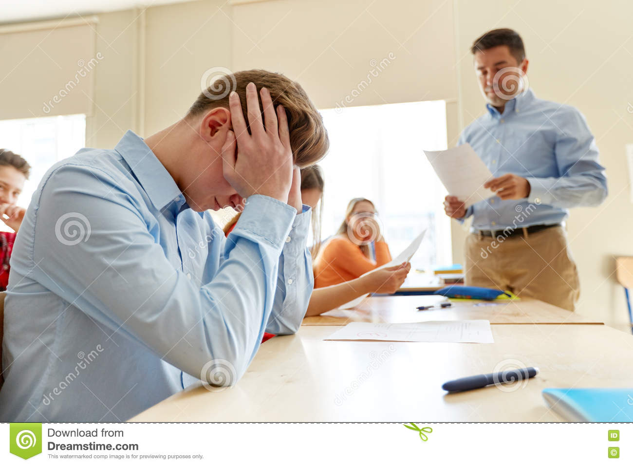 Teacher giving test results to group of students