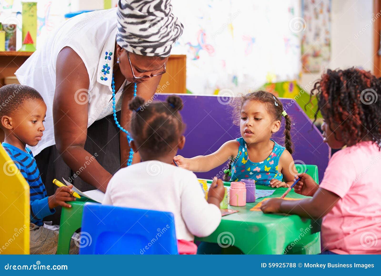 Teacher helping kids in a preschool class