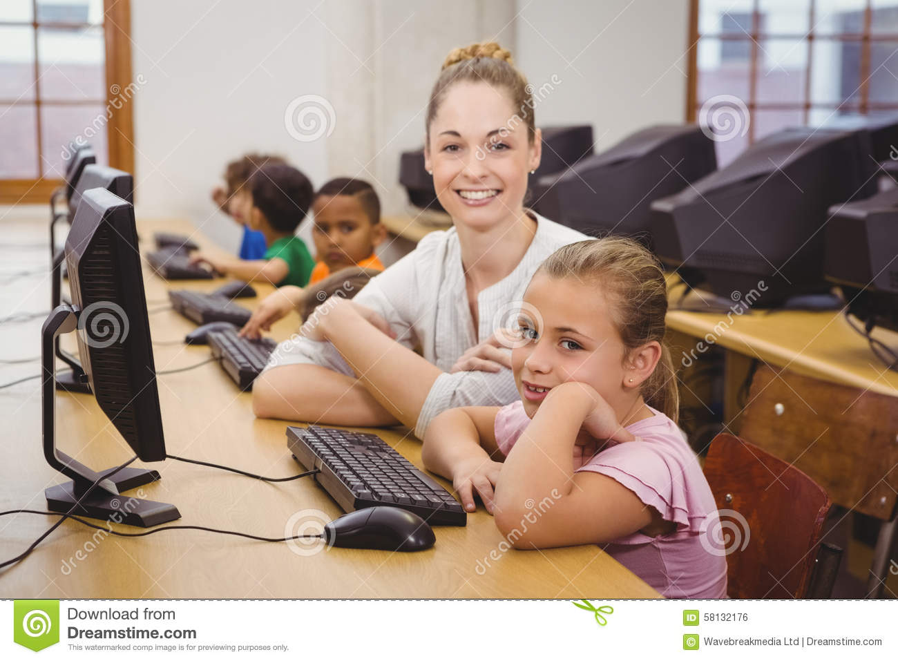 Teacher Helping A Student Using A Computer Stock Photo - Image of