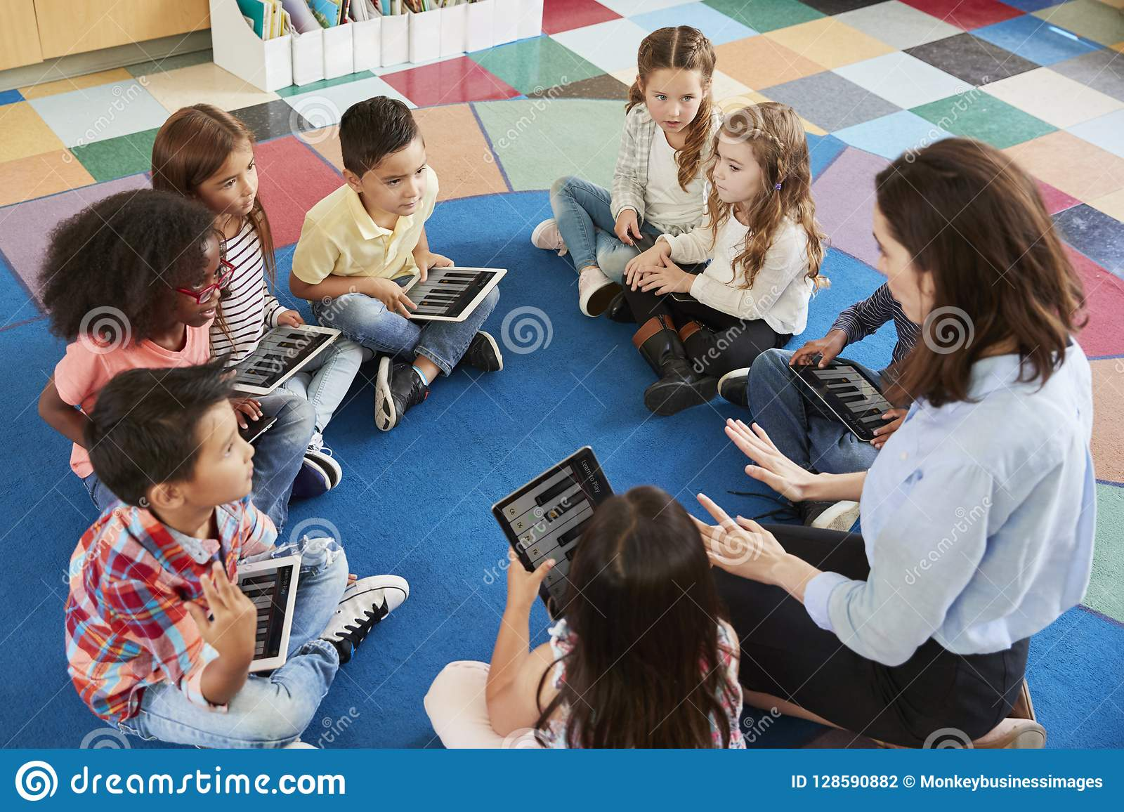 Teacher and kids in an elementary school lesson with tablets
