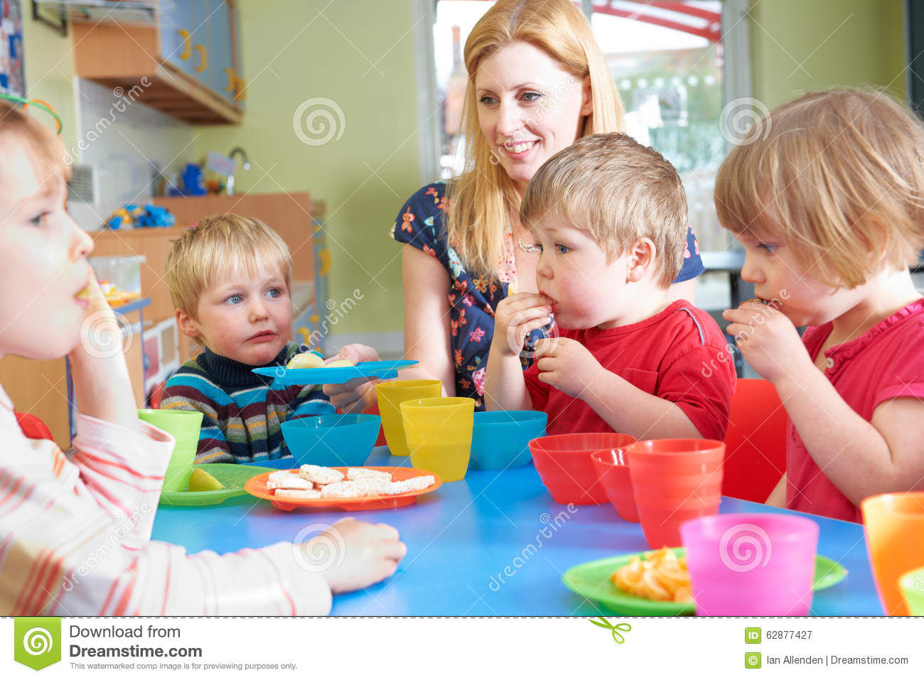 Teacher With Pre School Children Eating Healthy Snacks At