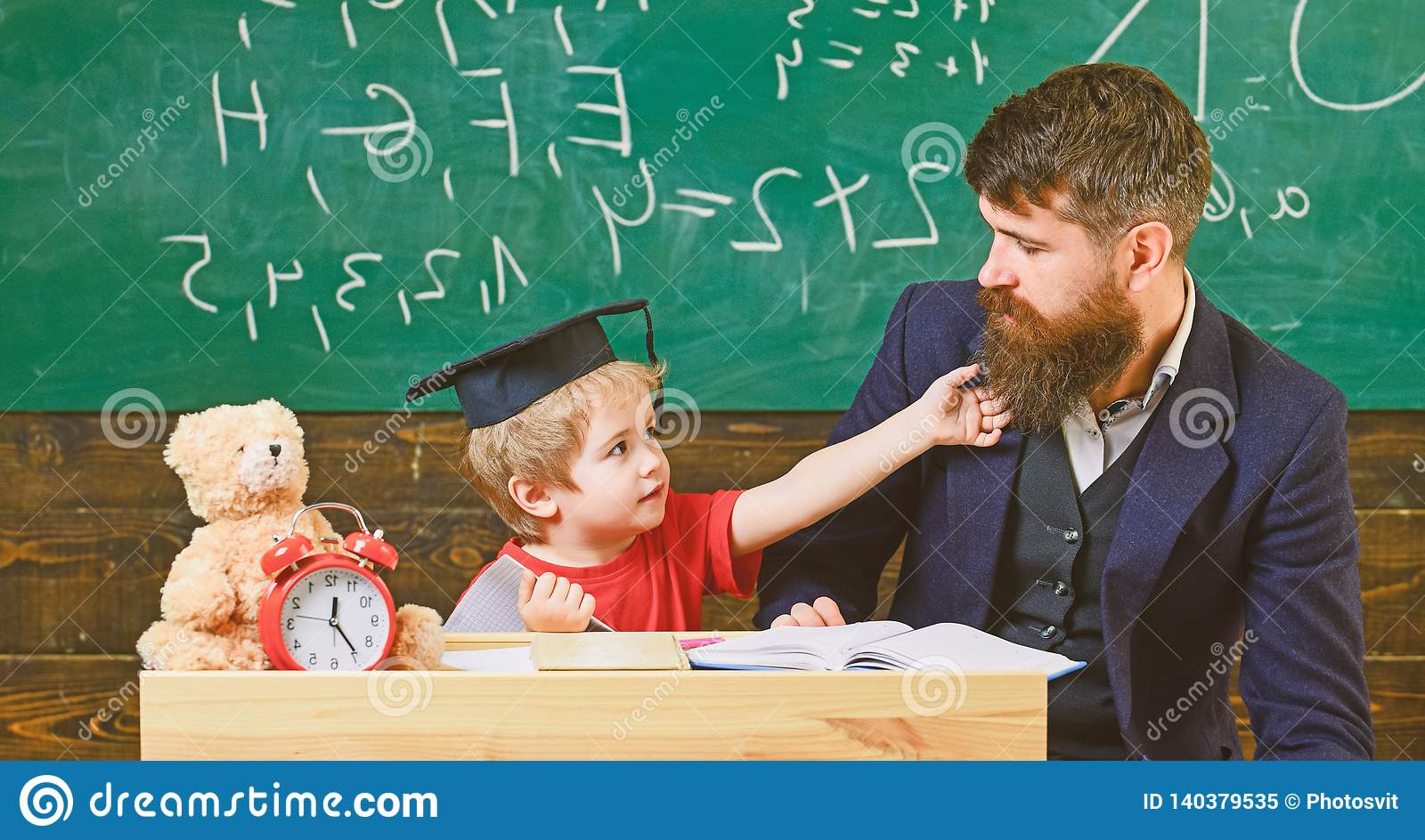 Teacher and pupil in mortarboard, chalkboard on background. Kid cheerful distracting while studying, attention deficit