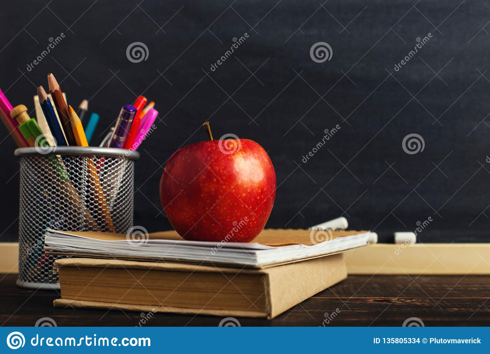 Teacher`s desk with writing materials, a book and an apple, a blank for text or a background for a school theme. Copy space