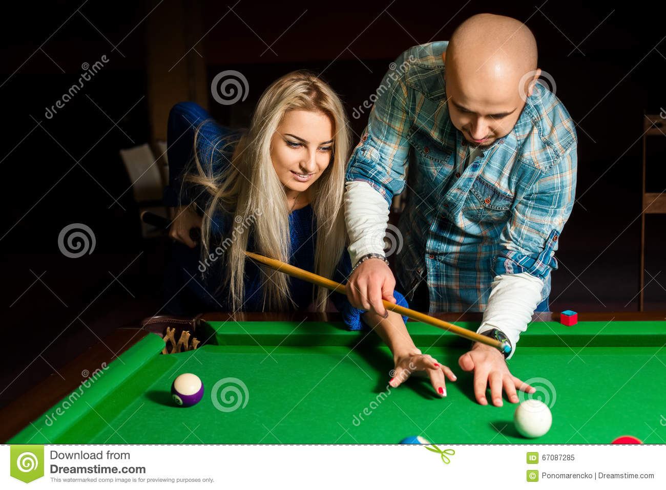 Teacher shows a girl how to play pool billiard stock photo for Pool game show