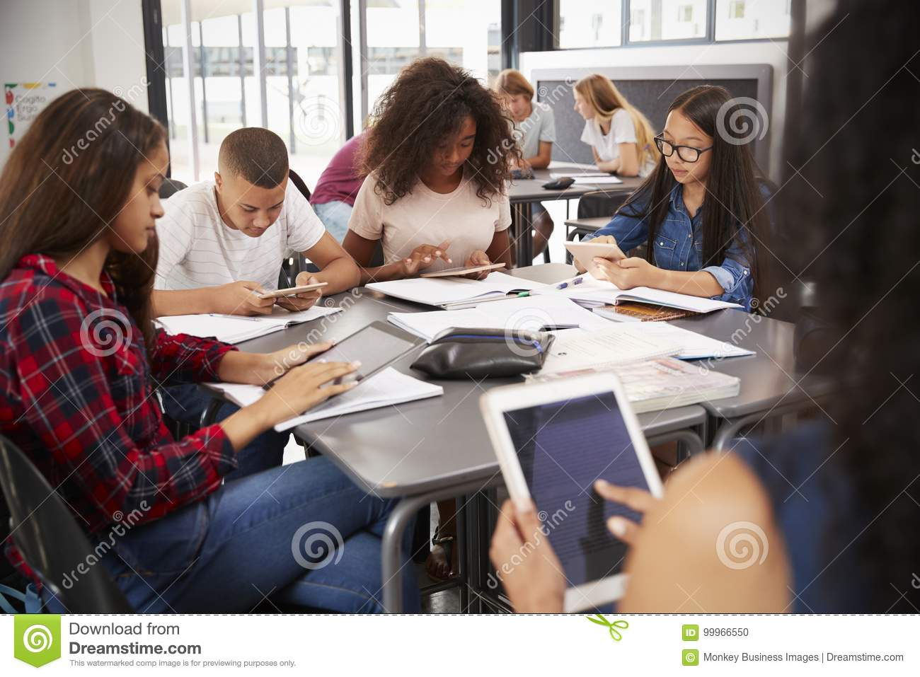 Teacher sitting with high school students using tablets