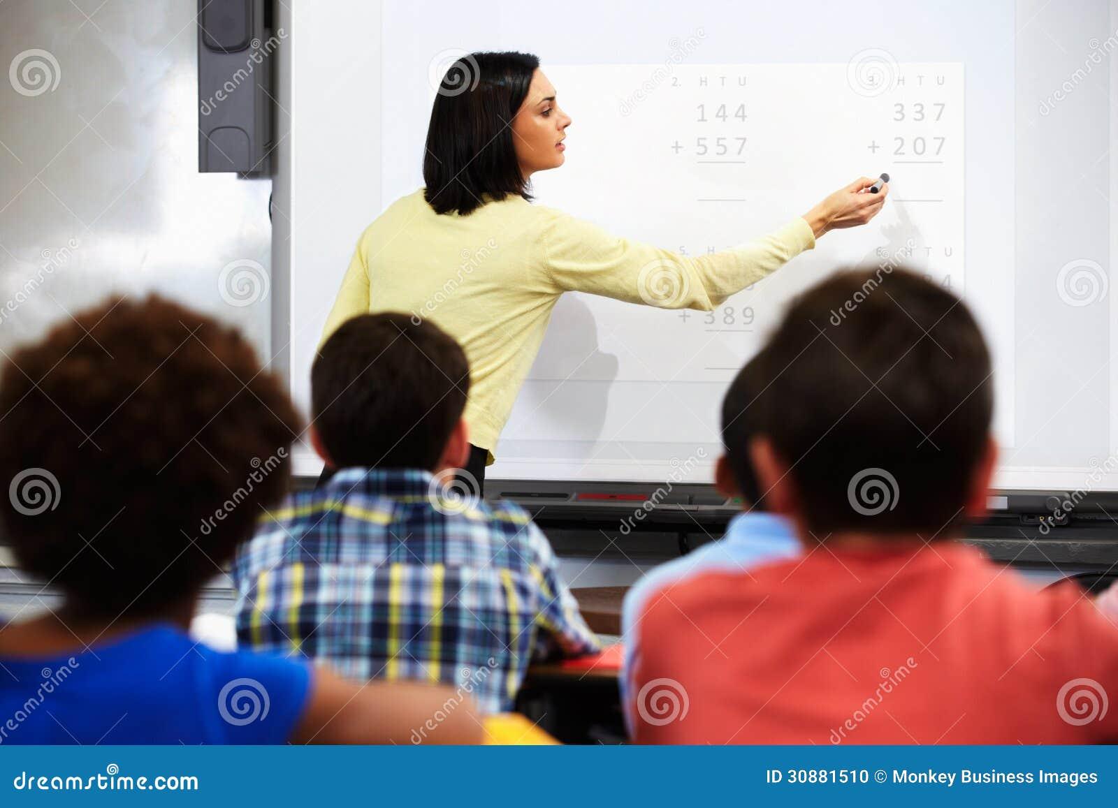 Teacher Standing In Class Using Interactive Whiteboard