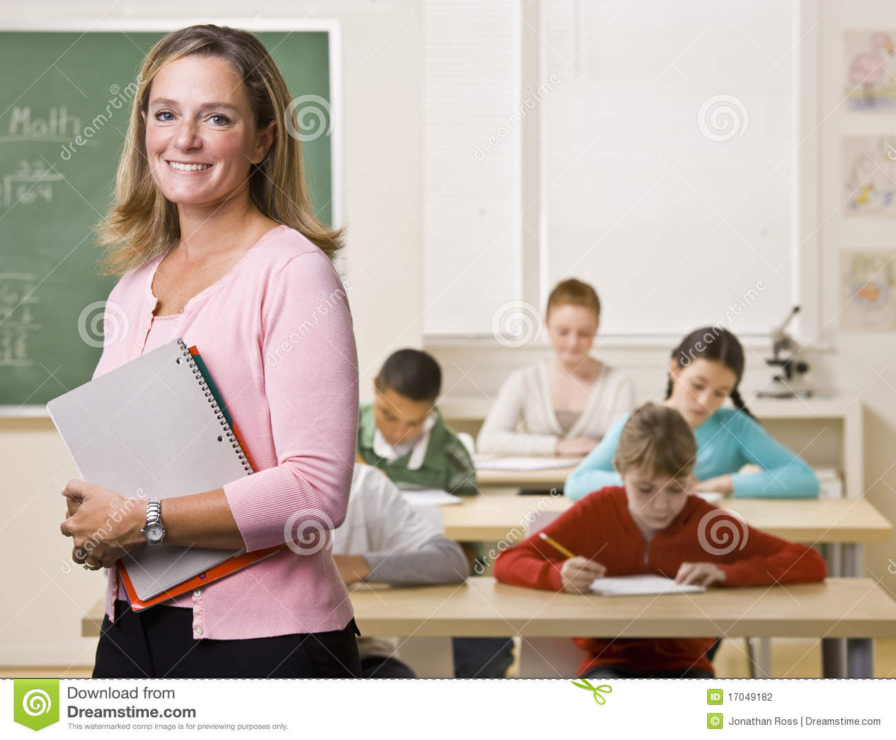 Teacher Standing With Notebook In Classroom Stock