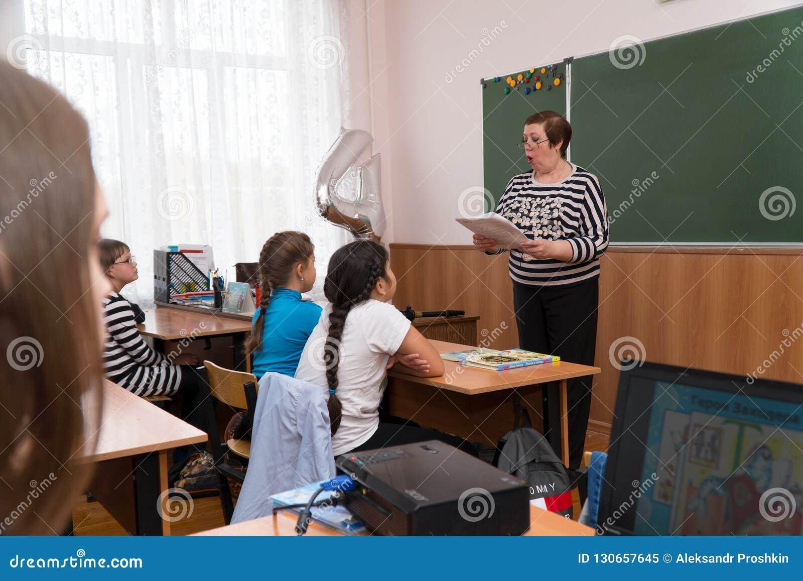 Teacher stands at the blackboard