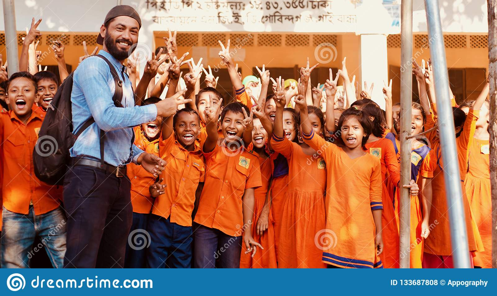 Teacher with the students showing victory sign