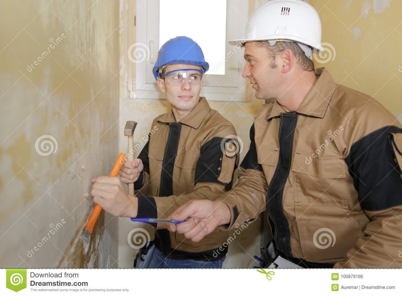 Teacher teaching student to use chisel and hammer