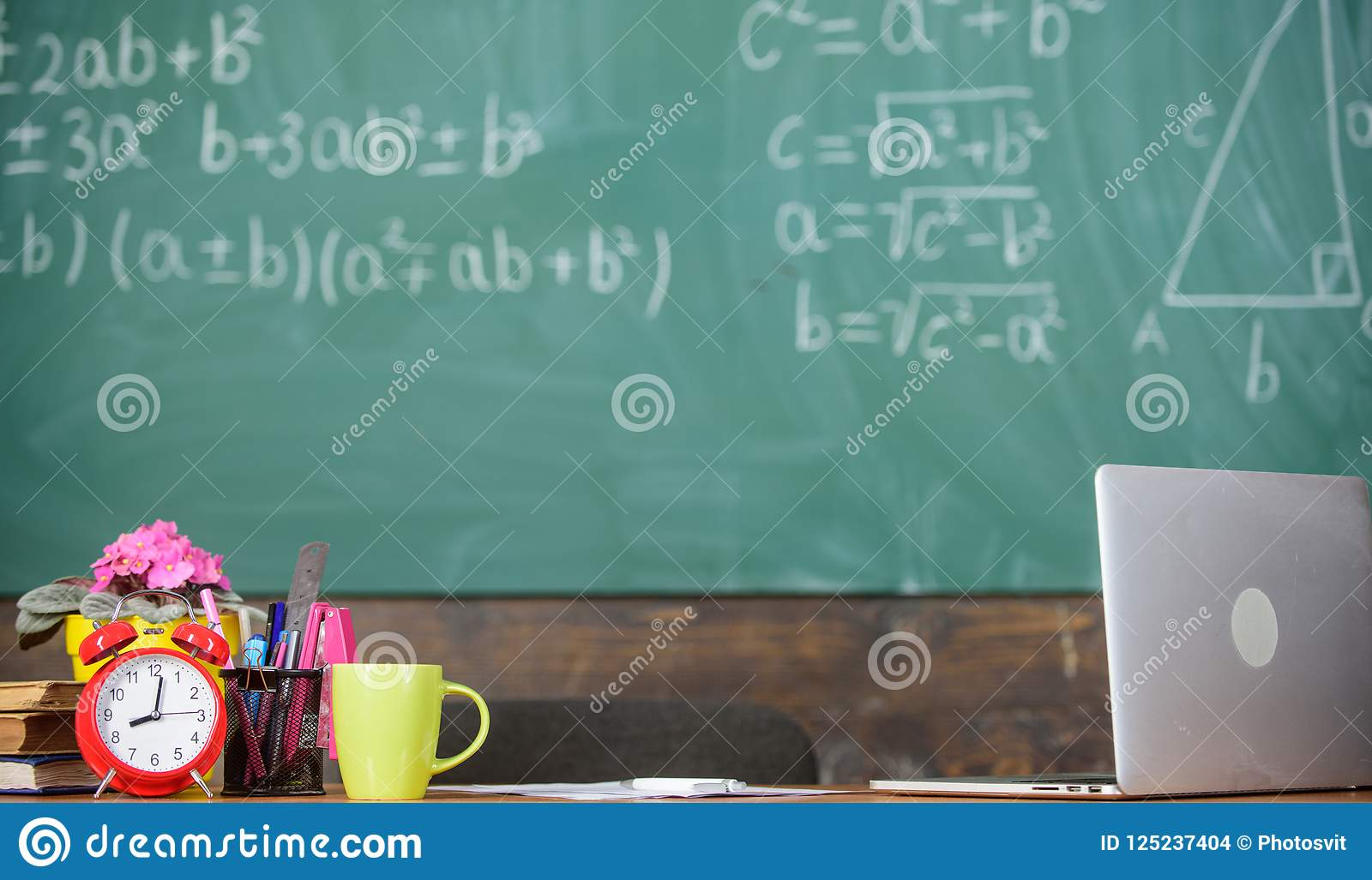 Teachers attributes. Working conditions which prospective teachers must consider. Table with school supplies alarm clock