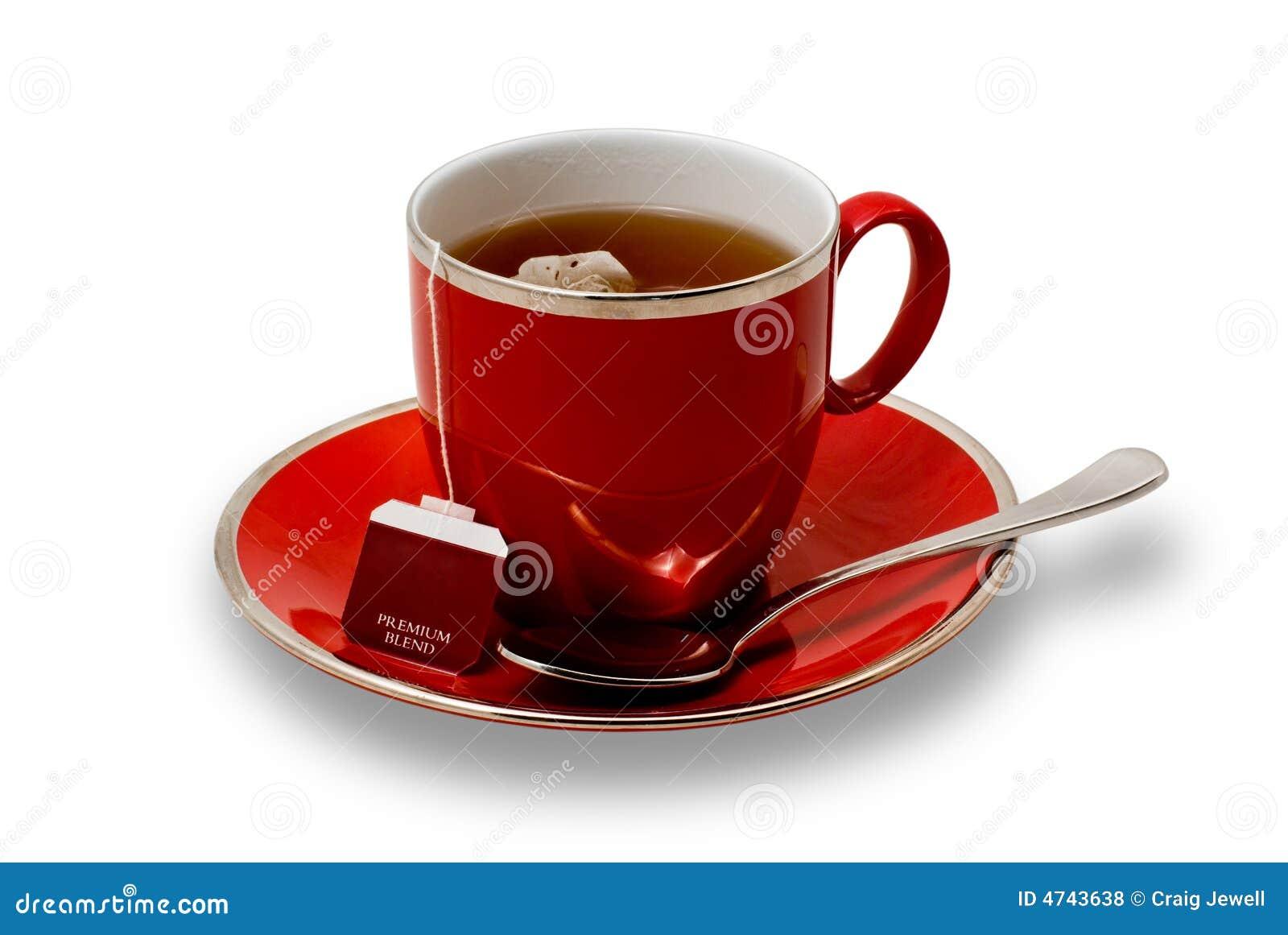 Teacup e Saucer vermelhos cheios com o Teabag isolado sobre
