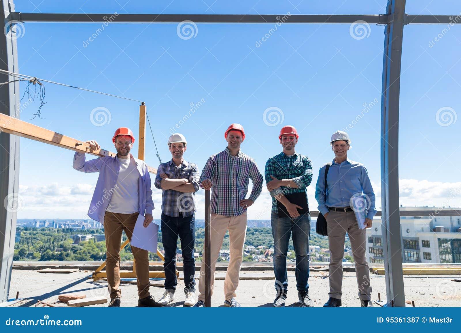 Team Of Builders On Costruction plats, lyckligt le ordförandeGroup In Hardhat utomhus partnerskap och teamworkbegrepp