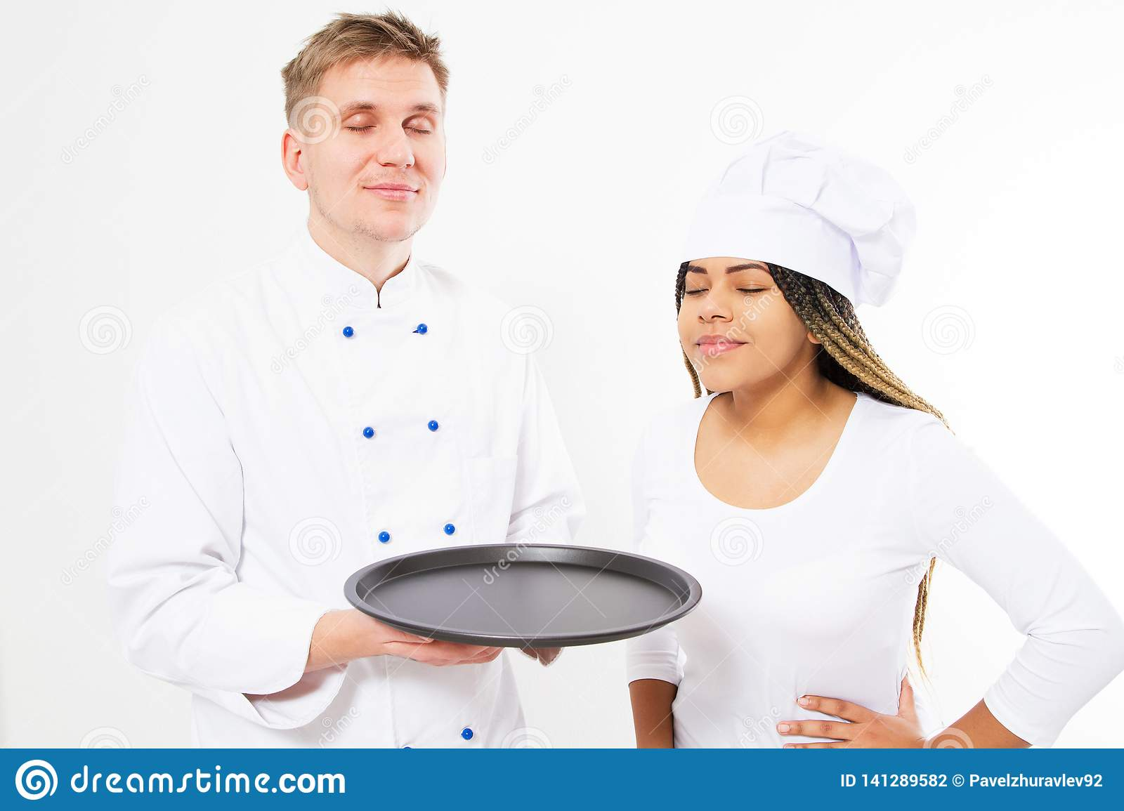 A team of chefs sniffs the pleasant aroma of something on an empty tray isolated on white