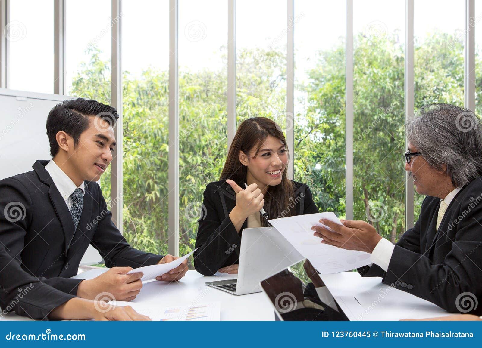Team des asiatischen Geschäfts aufwerfend im Konferenzzimmer Arbeits-brainstor