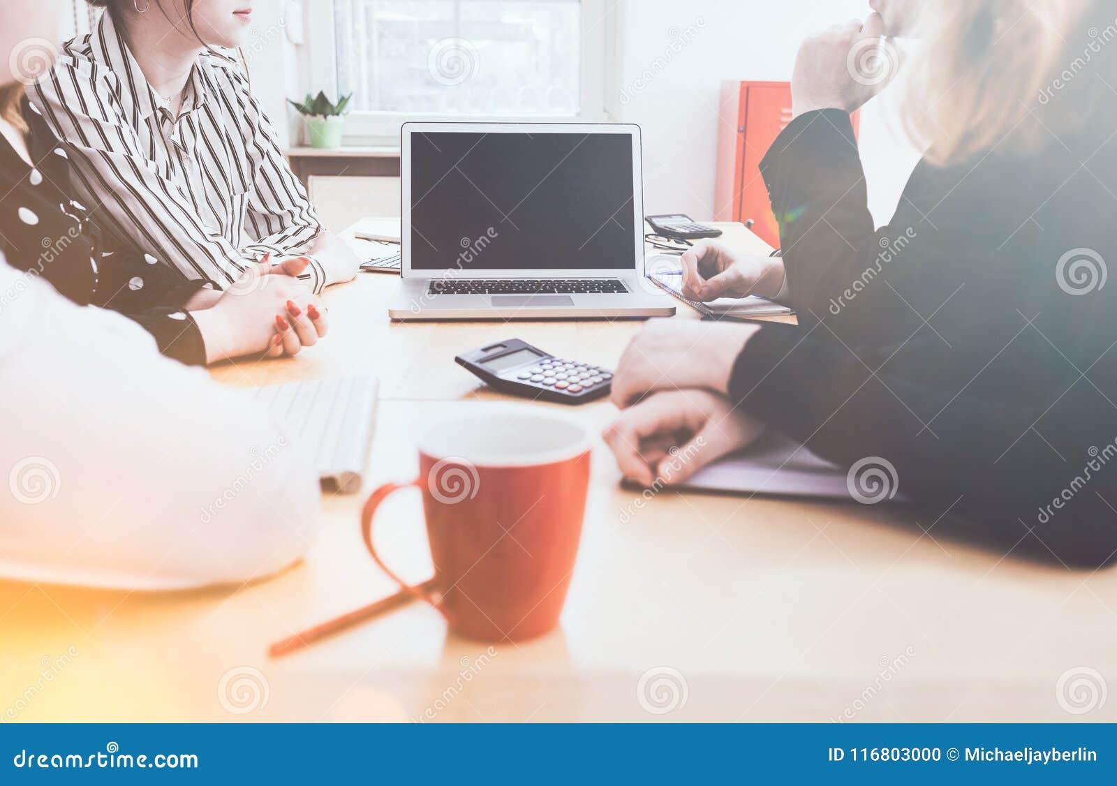 Team intorno al computer portatile con lo spazio della copia sullo schermo