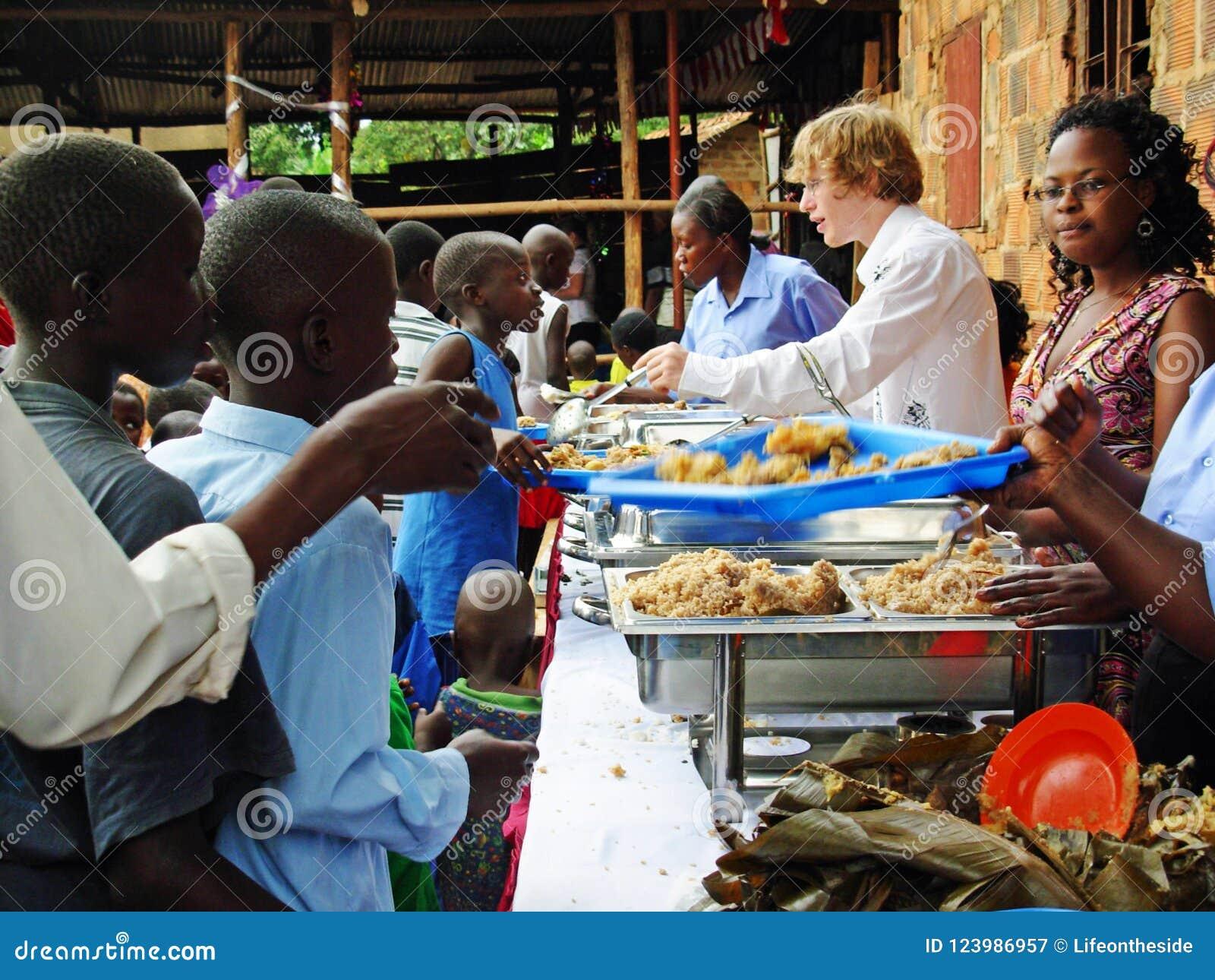 Team les travailleurs de volontaires de soulagement d aide alimentant aux enfants affamés l Afrique