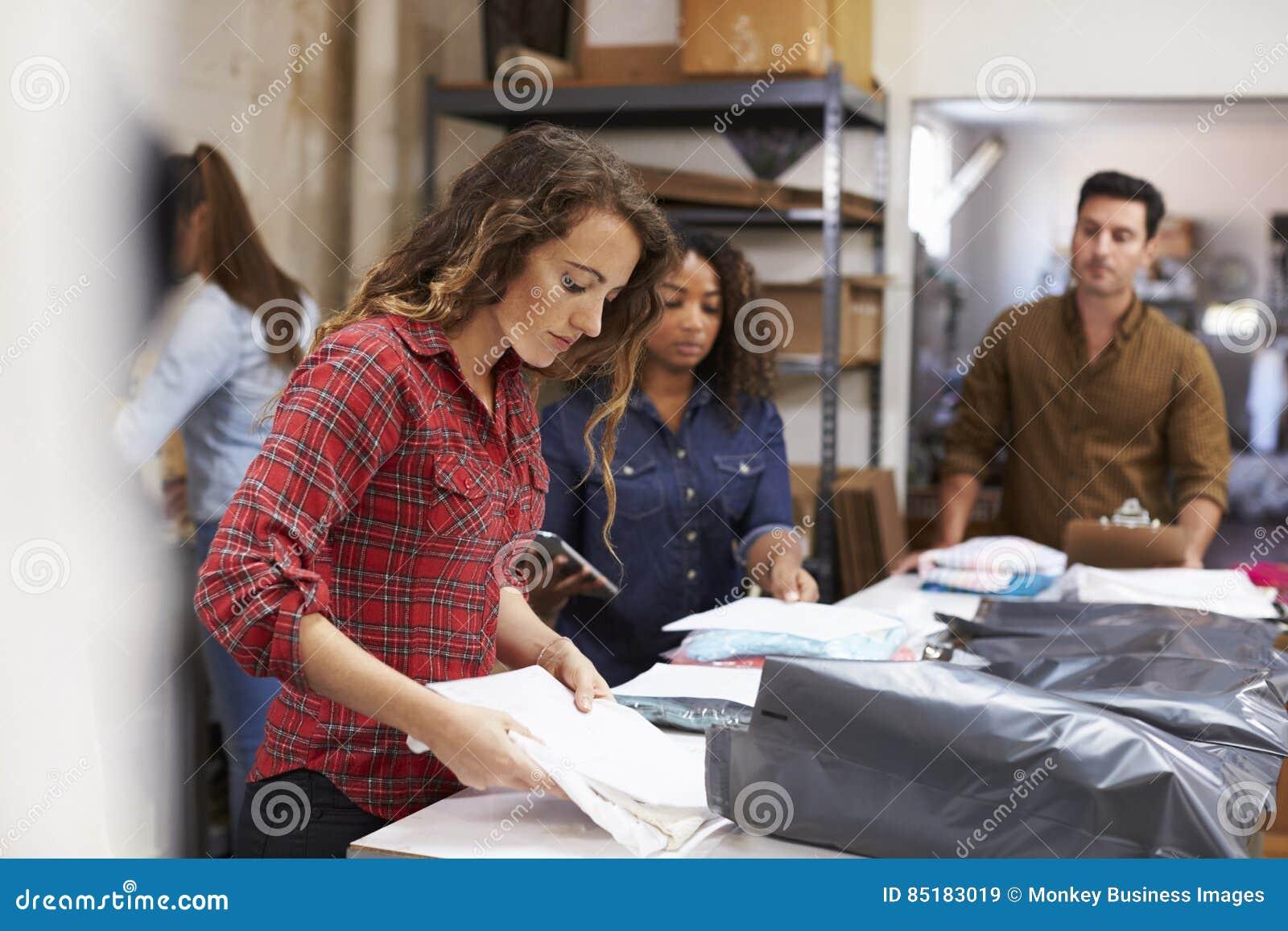 Team negli ordini dei vestiti della posta di un imballaggio della stanza per distribuzione