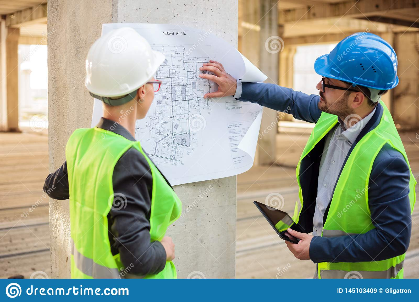 Two successful young architects looking at blueprints on a construction site