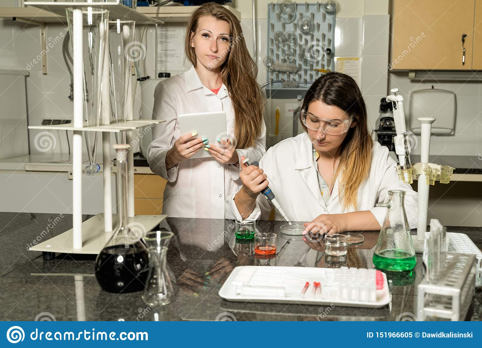 Team of two female laboratory technicians working in chemical or pharmaceutical laboratory