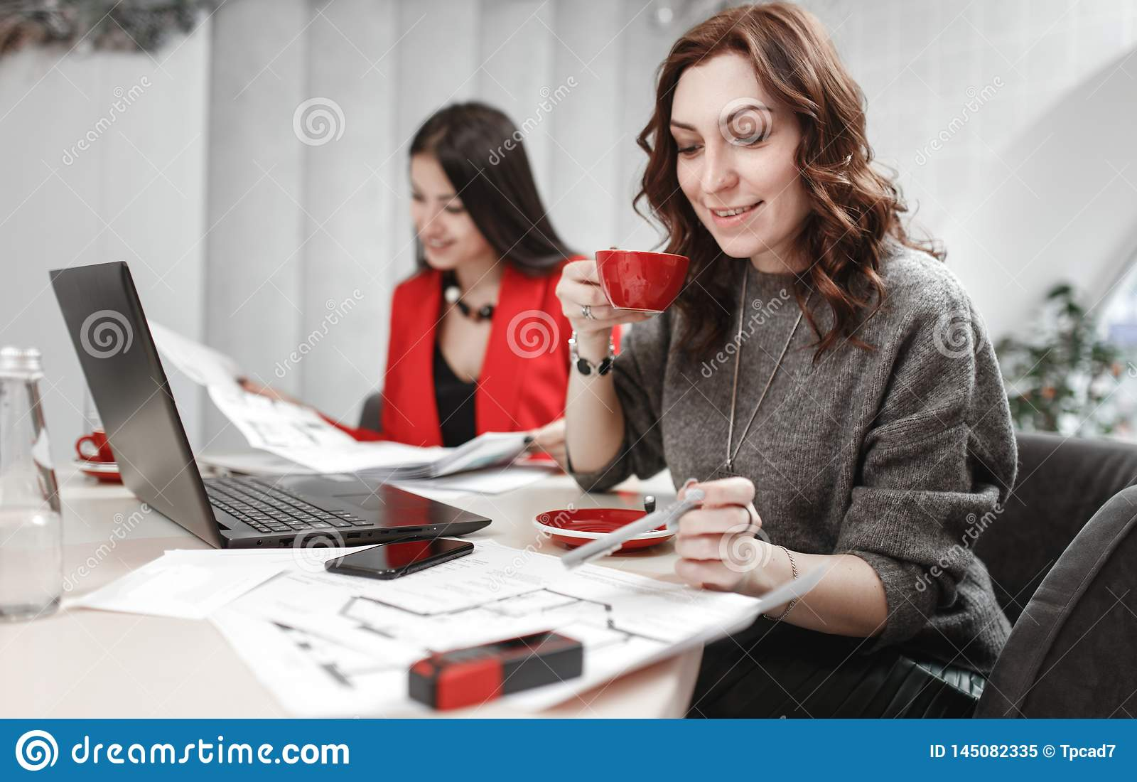 Team of two young women designer are working at the design project of interior sitting at the desk with laptop and