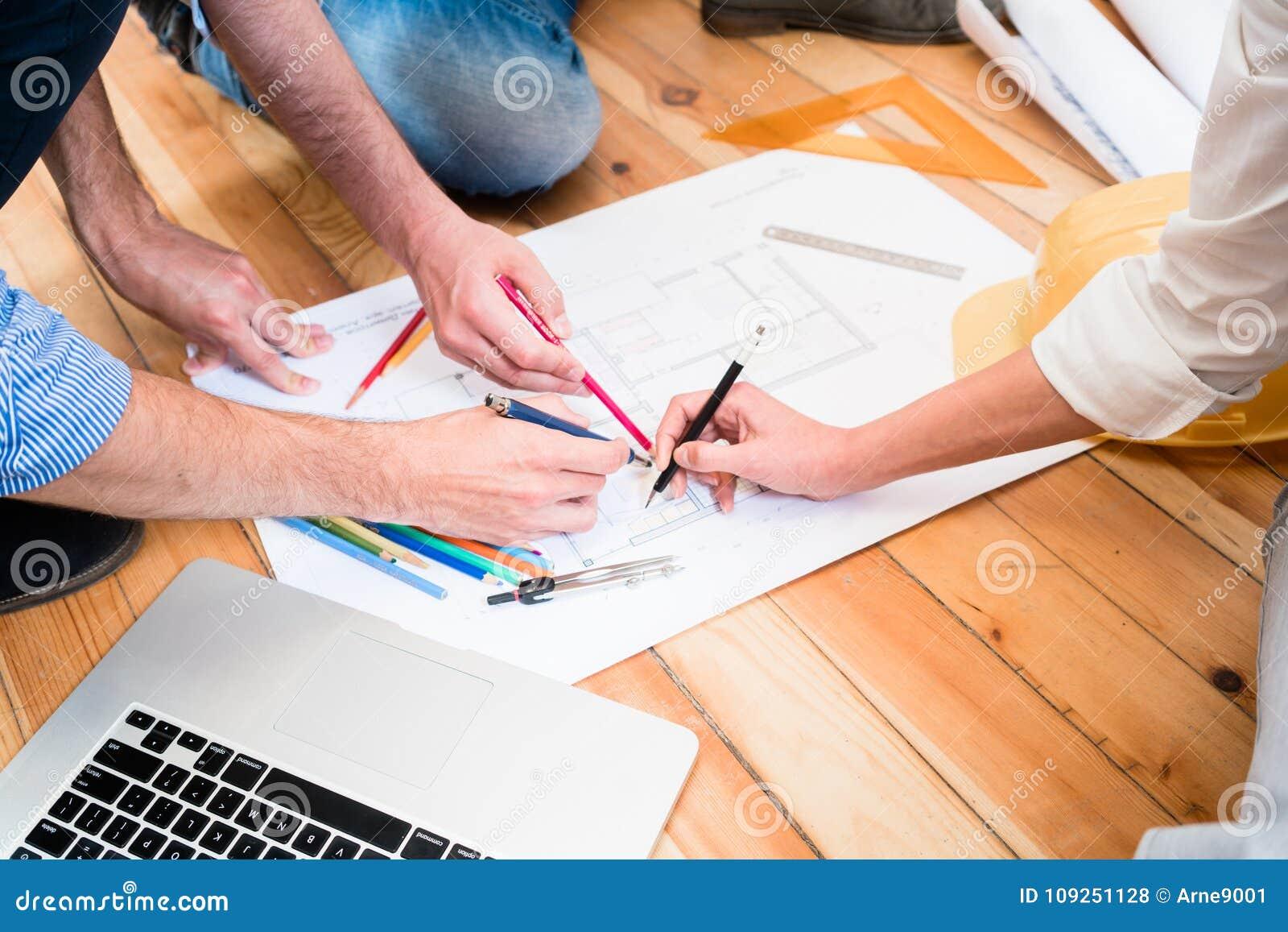 Team van architecten die op vloer met bouwplannen zitten