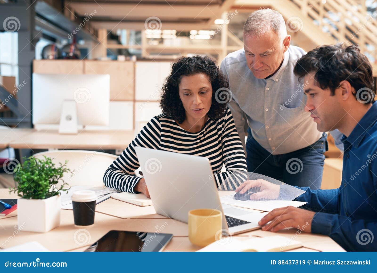 Team van bureaucollega s die zaken over laptop bespreken