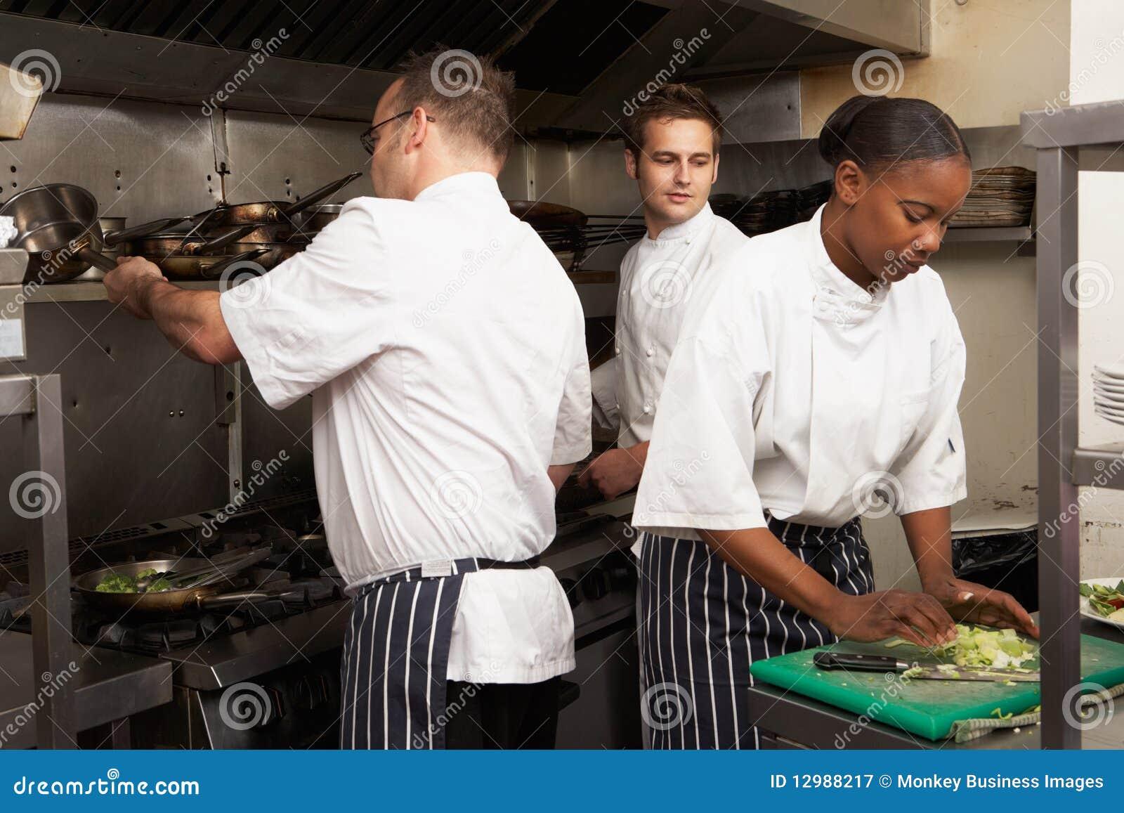Team van Chef-koks die Voedsel in de Keuken van het Restaurant voorbereiden