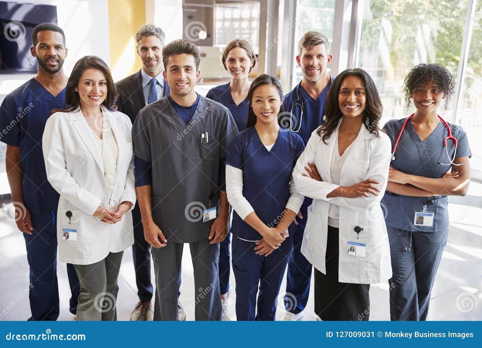 Team van gezondheidszorgarbeiders bij het ziekenhuis die aan camera glimlachen