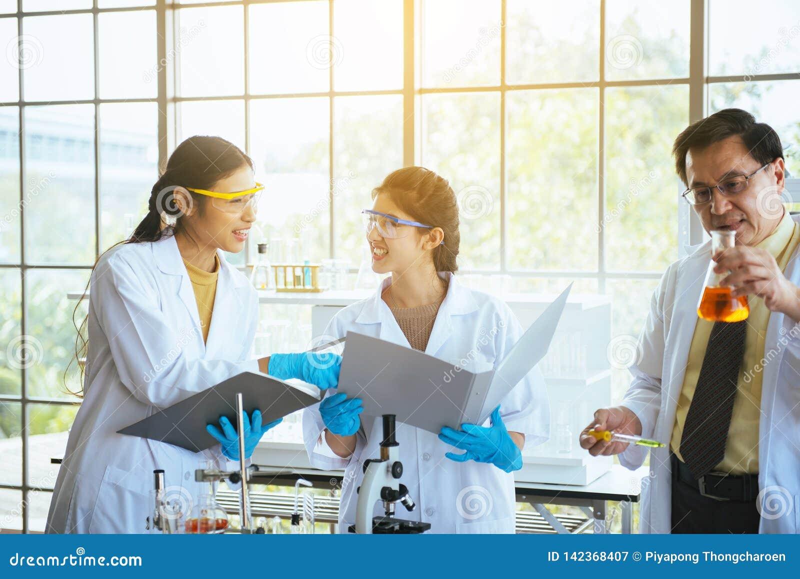 Team van jong Aziatisch het onderzoek nieuw project van de vrouwenchemicus met man professor bij laboratorium