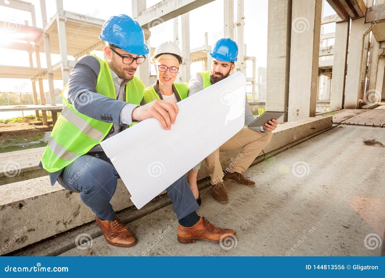 Team van succesvolle jonge architecten die plattegronden tijdens een vergadering bekijken