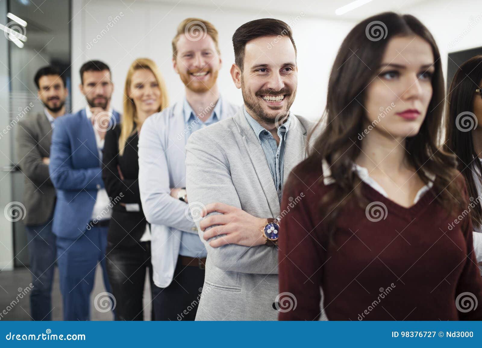 Team van vrolijk zakenlui die voor groepsbeeld stellen
