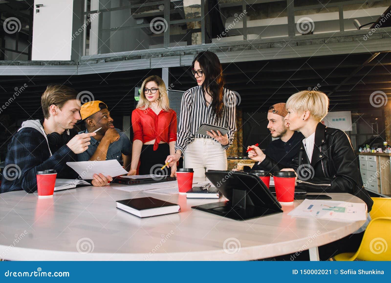 Team von den jungen Geschäftsfachleuten, die Technologie in einer informellen Sitzung engagiert auf Architektenentwurf einsetzen